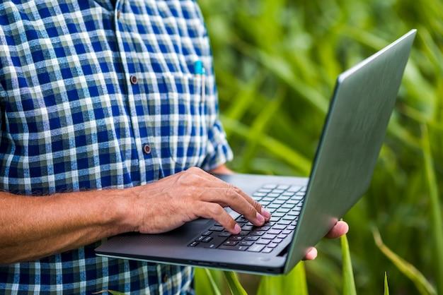 Chiuda sull'uomo con un computer portatile