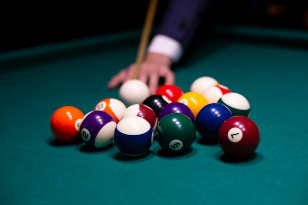 Close-up man with pool cue playing billiard