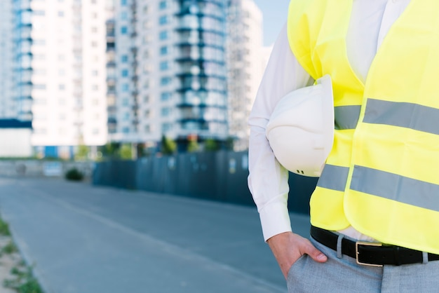 Close-up man with safety vest holding helmet