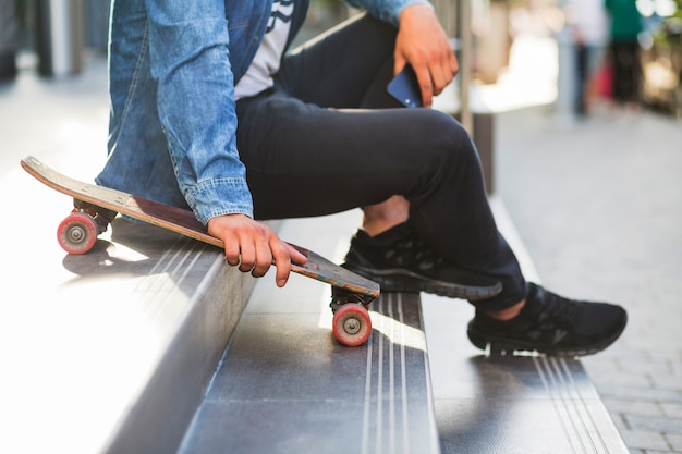 Close-up of a man with skateboard sitting on staircase