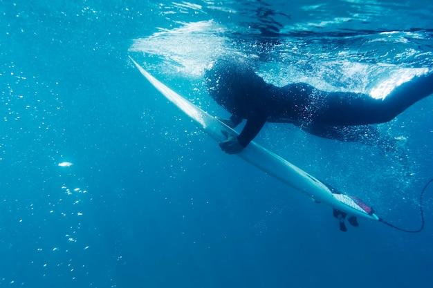 Крупным планом человек с доской для серфинга под водой