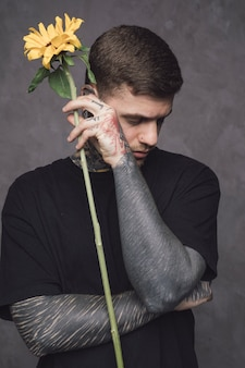 Close-up of a man with tattoo in his hand holding sunflower in hand against wall
