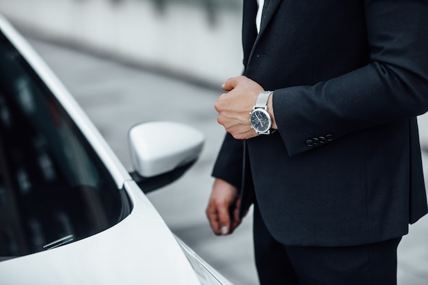 Close up of a man with a watch in his hand in a business suit near a premium white car