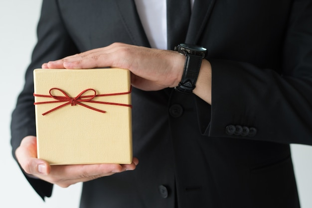 Close-up of man with wristwatch holding gift box