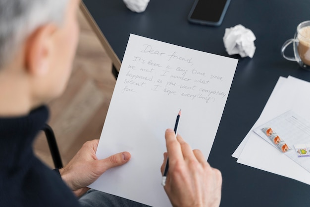 Крупным планом человек, пишущий письмо