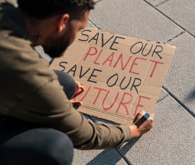 Крупным планом человек пишет плакат