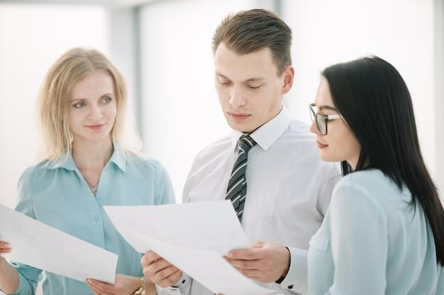 비즈니스 문서에 대해 논의하는 관리자와 직원을 닫습니다.