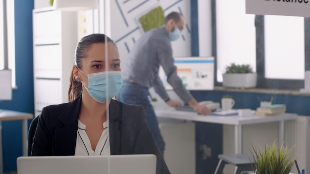 Close up of manager discussing with coworker looking at business statistics while wearing medical face mask. team sitting in new normal office respecting social distance during coronavirus pandemic