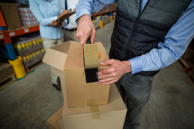 Close up of manager hands taping up a cardboard box