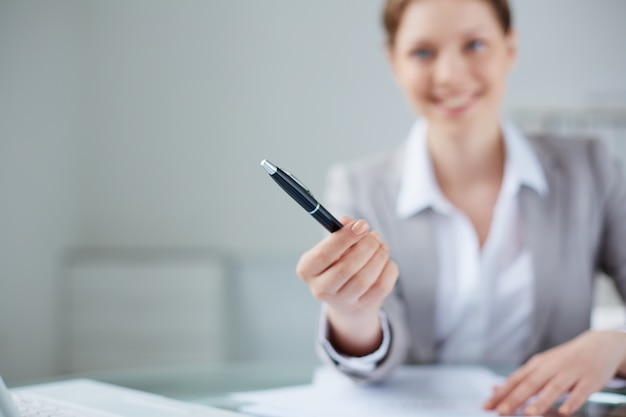 Close-up of manager holding a pen with blurred background