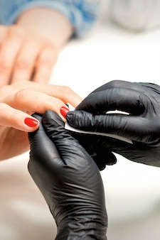 Close up of manicure master leaks female red nails with a lint-free napkin in a nail salon