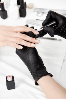 Chiuda in su delle mani del manicure in guanti che applicano la lucidatura del gel.