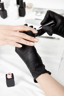 Close up of manicurist hands in gloves applying gel polish.