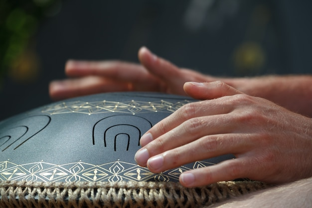 Close-up of a mans hand playing on modern musical instrument hand pan or vadjraghanta or metal tongue drumon, selective focus