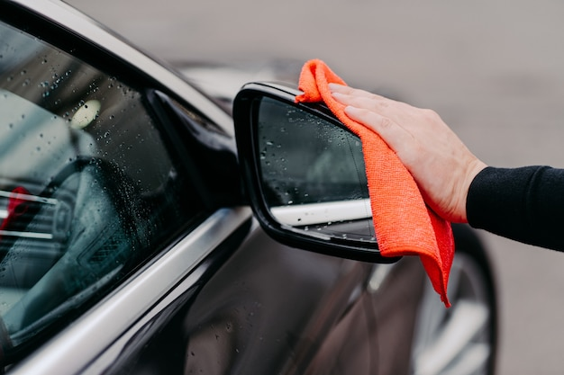 Close up of mans hand wiping water on black car with microfiber cloth. focus on auto side mirror. transporation self service