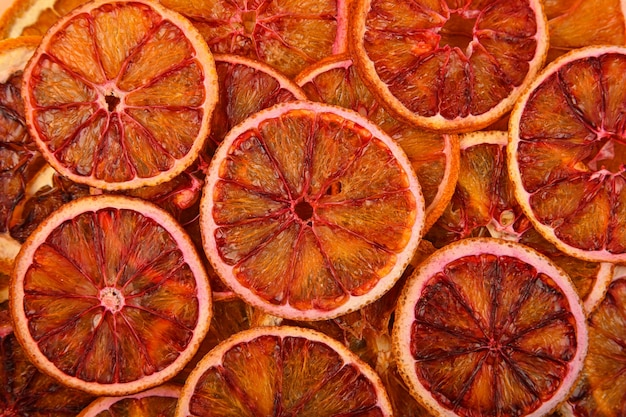 Close up many dried crispy red blood orange ring chips on retail display, elevated top view, directly above