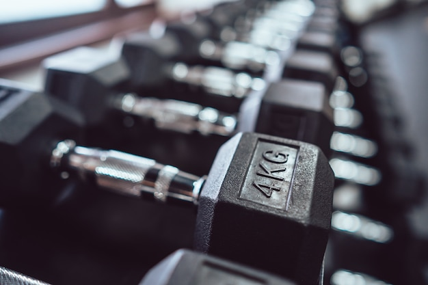 Close up of many metal dumbbells on rack in sport fitness center.