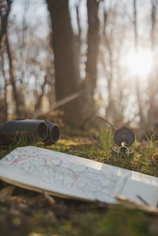 Close-up of map, binoculars and compass on the grass