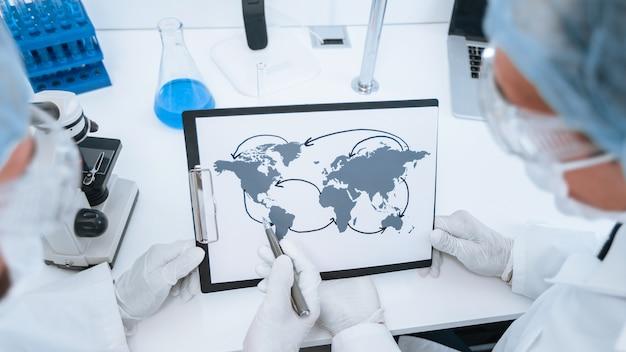 확대. 전염병 학자의 손에있는 코로나 바이러스 확산지도. 건강 보호의 개념. nasa에서 제공 한이 이미지의 요소