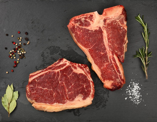 Close up marbled raw ribeye and porterhouse t bone beef steaks on black slate cutting board with spices to season, elevated top view, directly above