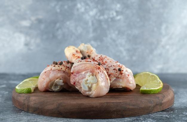 Close up cosce di pollo marinate con fette di lime su tavola di legno.