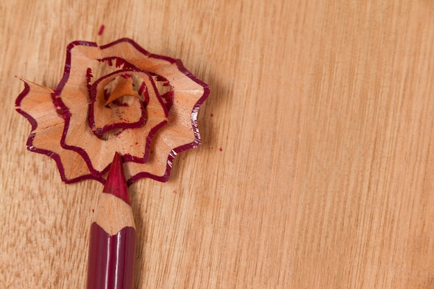 Close-up of maroon colored pencil with shavings