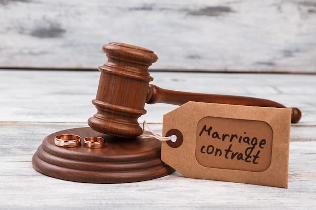 Брачный контракт крупным планом и деревянный молоток. фон белый стол.