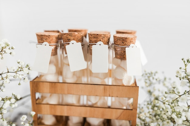 Close-up of marshmallow test tubes with tag in crate on marble background