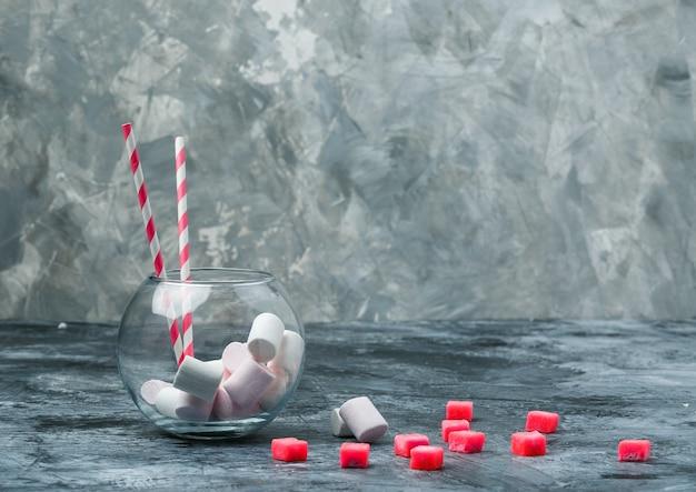 濃紺と灰色の大理石の表面にキャンディーと赤いギンガムチェックのテーブルクロスが入った瓶に入ったマシュマロとサトウキビのクローズアップ。テキスト用の水平方向の空き領域