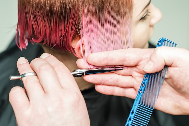 Close up of a masculine hand is cutting pink hair with scissors.