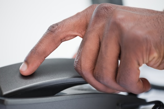 Close up of a masculine hand on a phone handset