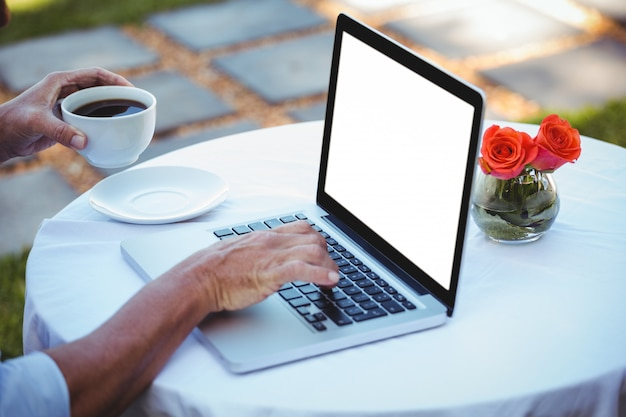 Close up of masculine hands using laptop and having coffee