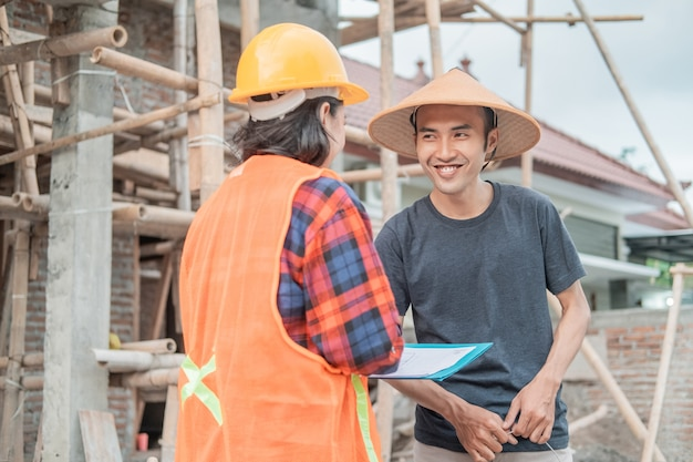 Close up of mason smiling at female constructor during discussion about building sketches in building construction background