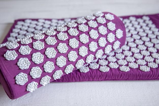 베개와 흰색 마사지 팁이있는 마사지 침술 매트, 휴식과 치료를위한 마사지 매트를 닫습니다.