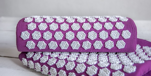 Close up massage acupuncture mat with pillow and white massage tips, massage mat for relaxation and treatment