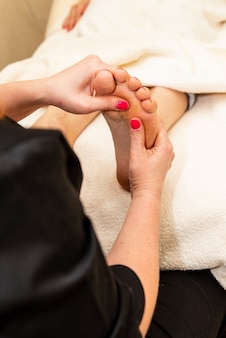 Close up of masseuse doing foot reflexology to woman at spa. therapist hands doing foot massage at wellness center. woman receiving a feet massage at health spa.