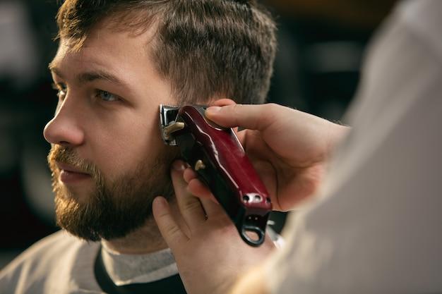 마스터 이발사를 닫고, 스타일리스트는 남자, 젊은이에게 헤어 스타일을합니다. 전문 직업, 남성 아름다움 개념. 고객의 머리카락, 콧수염, 수염 관리. 부드러운 색상과 초점, 빈티지.