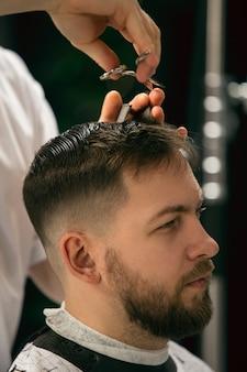 Крупным планом мастер-парикмахер, стилист делает прическу парню, молодому человеку. профессиональное занятие, понятие мужской красоты. ухаживает за волосами, усами, бородой клиента. мягкие цвета и акцент, винтаж.