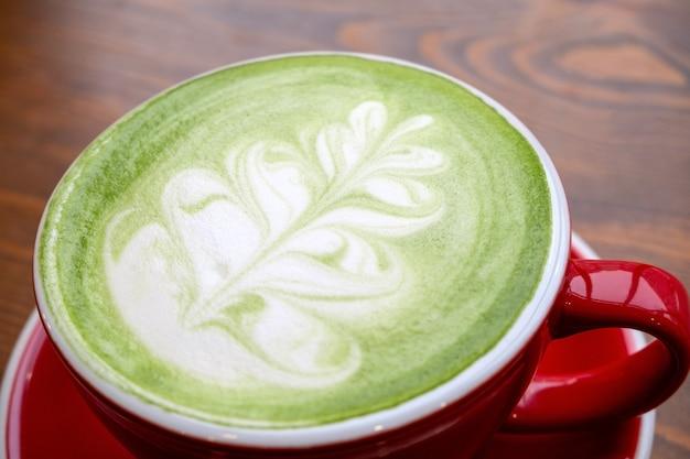 Close up   match tea latte with a latte art in red ceramic mug in a coffee shop