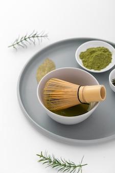 Close-up matcha powder and bamboo whisk