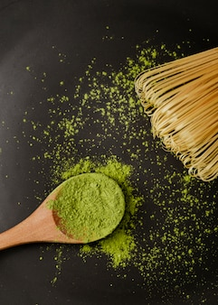 Close-up of matcha tea powder in wooden spoon with bamboo whisk