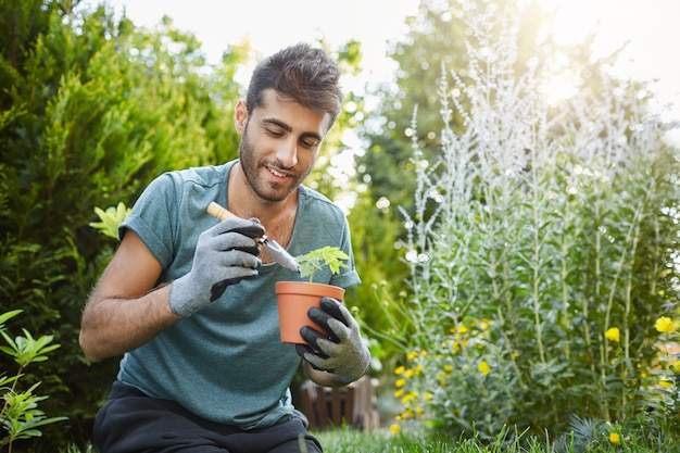 Close up of mature bearded caucasian man in blue t-shirt planting flowers in pot with garden tools,spending peaceful morning in garden hear house.