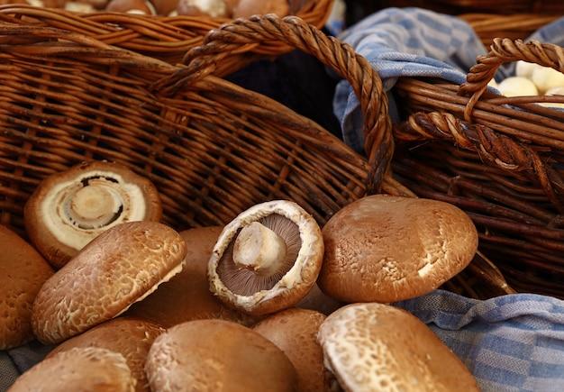Крупным планом зрелые коричневые съедобные грибы портобелло (agaricus bisporus) в плетеной деревянной корзине на розничной выставке, вид под высоким углом