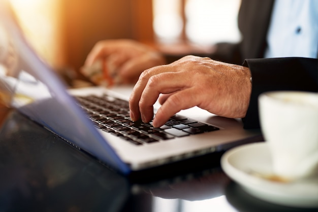 Close up mature professional elegant businessman is using tablet and drinking coffee