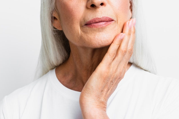 Close-up mature woman applying skin care