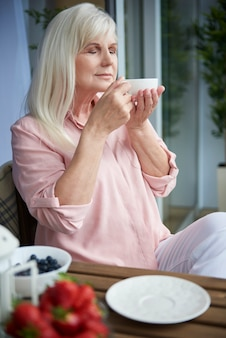 Close up on mature woman enjoying good coffee on the balcony