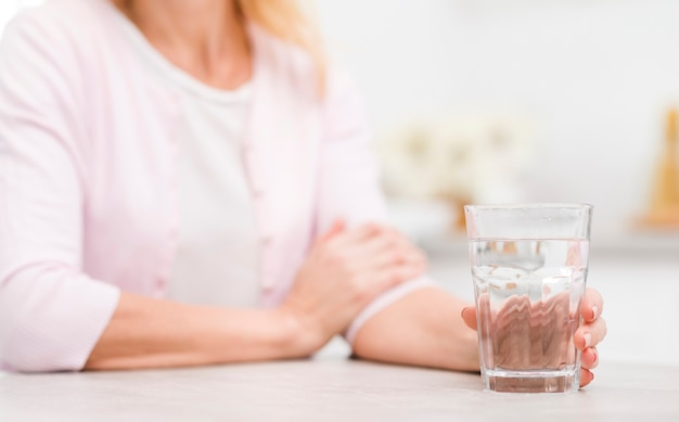 Close-up mature woman holding a glass of water