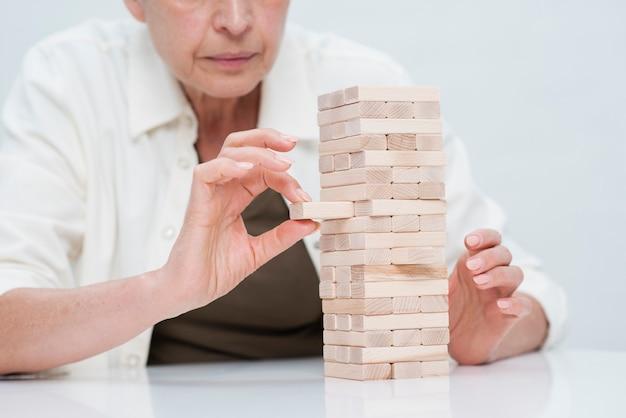 Close-up mature woman playing jenga
