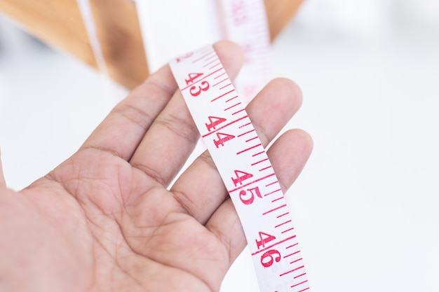 Close up measure tape in man hand.