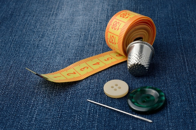 Close-up of measuring tape of buttons and thimble.